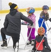 skating instructor on ice with three young children