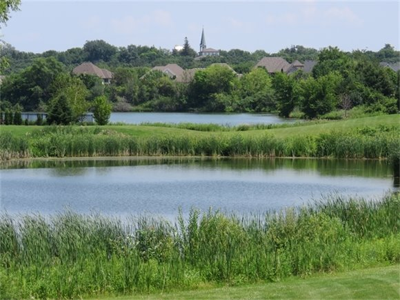 lake with houses and church steeple in background