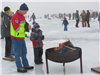 adult and child warming themselves around fire at ice fishing event on stieger lake