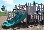 Children Playing on a Green Slide at a Playground