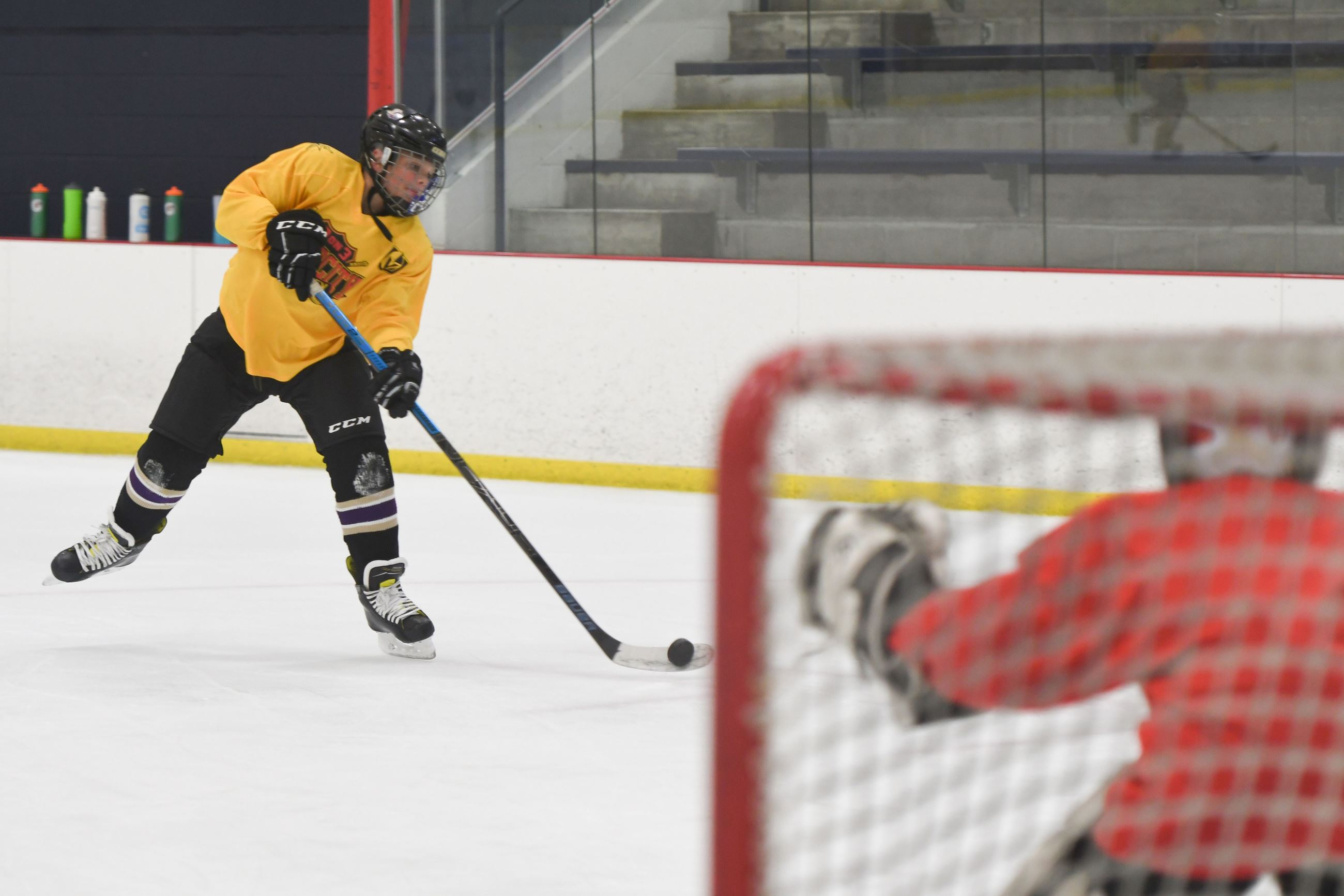 Kid shooting puck at goalie