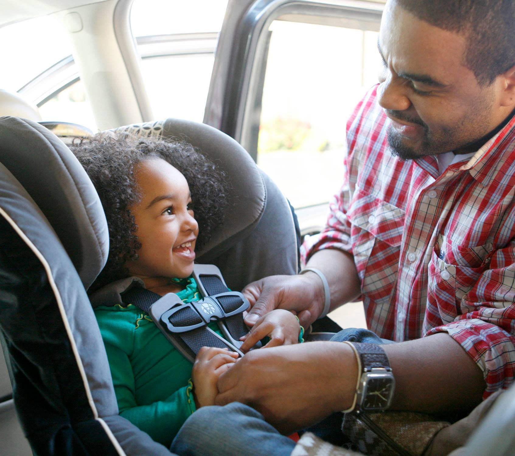 father buckling child into car seat