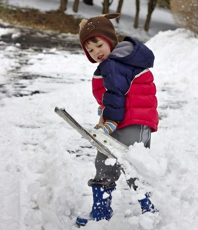Child using snow shovel to remove snow