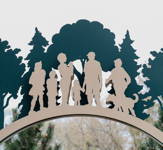 A sculpture with a group of people and trees in silhouette.