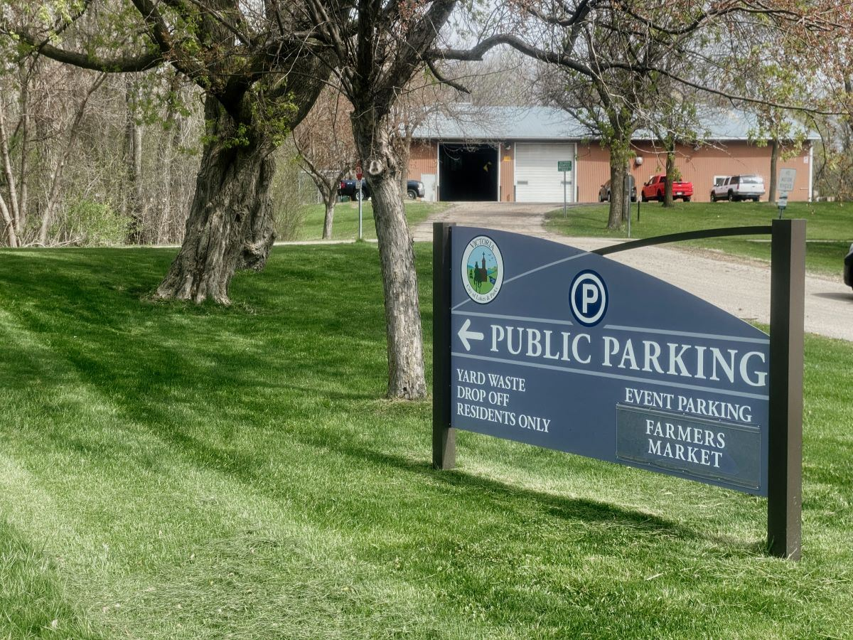An image of a sign for public parking with a building in the background.